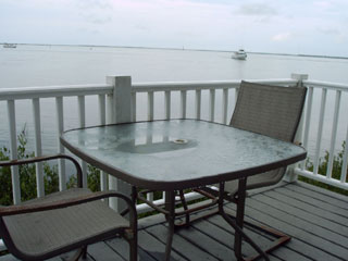 Relax and enjoy the island bay views on a waterfront lodge porch at the KOA